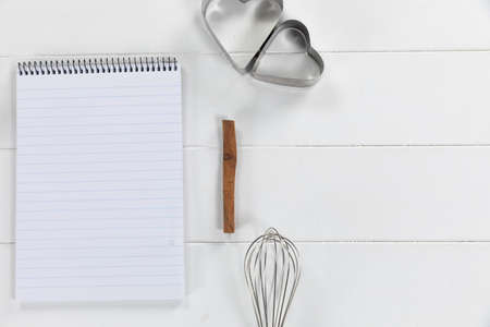 Top view of a composition with an empty page in notebook with cookie cutters and whisker, arranged on on a white textured wooden surface