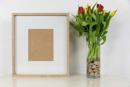Close up view of an empty picture frame, with red and yellow tulips placed in a glass vase arranged on a plain white background