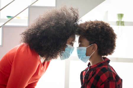 Mixed race mother with son enjoying family time together at home, social distancing and self isolation in quarantine lockdown, standing by the stairs, wearing face masks