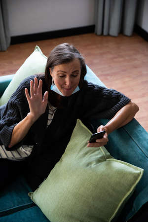 Caucasian woman enjoying time at home, social distancing and self isolation in quarantine lockdown, sitting on sofa, using a smartphone and waving during video call.