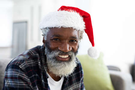Portrait of African American man at home sitting on a sofa in the living room at Christmas, smiling to camera wearing a hat. Social distancing and self isolating during Covid 19 pandemic.