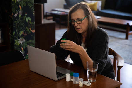 Caucasian woman enjoying time at home, social distancing and self isolation in quarantine lockdown, sitting at table, using a laptop, holding container with medication.