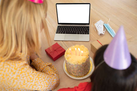 Caucasian woman and her daughter spending time at home, sitting by table, using laptop, wearing birthday hats. Social distancing during Covid 19 Coronavirus