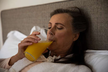 Caucasian woman spending time at home, social distancing and self isolation in quarantine lockdown, lying in bed drinking orange juice.