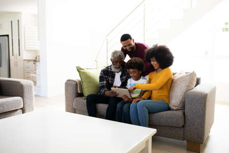 Multi-generation African American family spending time at home together, using digital tablet on sofa in living room. Quality family spending quality time at home together. 版權商用圖片