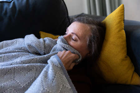 Caucasian woman enjoying time at home, social distancing and self isolation in quarantine lockdown, sleeping on sofa cover with blanket.