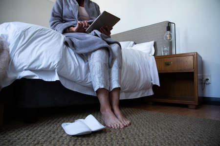 Low section of Caucasian woman enjoying time at home, social distancing and self isolation in quarantine lockdown, sitting on bed, using a digital tablet in bedroom.