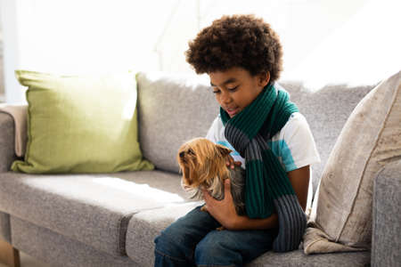African American boy with afro hair spending time at home, holding a pet dog and smiling, sitting on sofa. Social distancing and self isolating at home during Coronavirus Covid 19 quarantine lockdown.