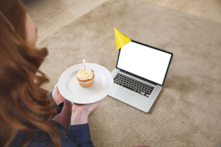 Caucasian woman spending time at home, in living room, using laptop, celebrating and holding a cupcake with a candle. Social distancing during Covid 19 Coronavirus quarantine lockdown.