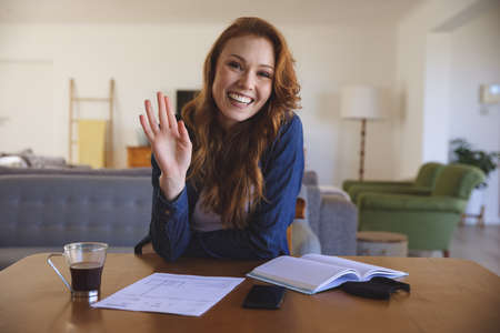 Portrait of a Caucasian woman spending time at home, in living room, smiling and waving, working from home. Social distancing during Covid 19 Coronavirus quarantine lockdown.