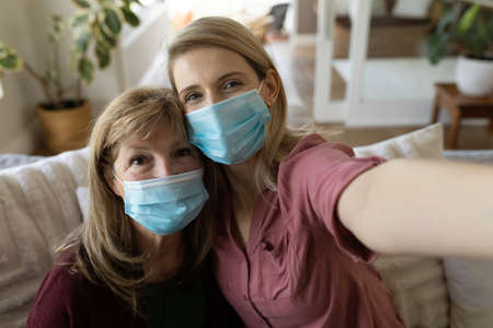 Senior Caucasian woman spending time at home with adult daughter, sitting on couch talking and using smartphone, taking selfie. Social distancing during Covid 19 Coronavirus quarantine