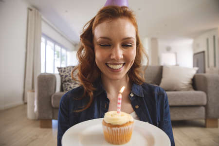 Caucasian woman spending time at home, in living room, smiling, celebrating and holding a cupcake with a candle. Social distancing during Covid 19 Coronavirus quarantine lockdown. Banco de Imagens