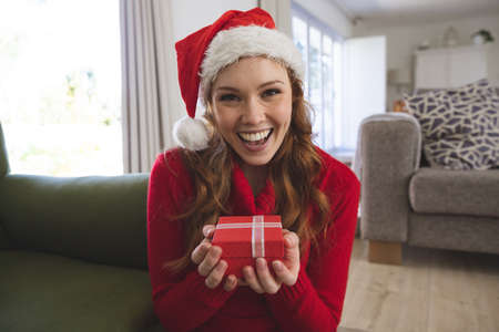 Portrait of Caucasian woman spending time at home, in living room, smiling, wearing Christmas hat, holding a gift box. Social distancing during Covid 19 Coronavirus quarantine lockdown. Banco de Imagens