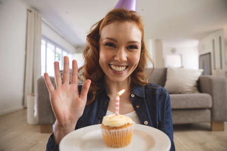 Portrait of Caucasian woman spending time at home, in living room, smiling, celebrating and holding a cupcake with a candle. Social distancing during Covid 19 Coronavirus quarantine lockdown.