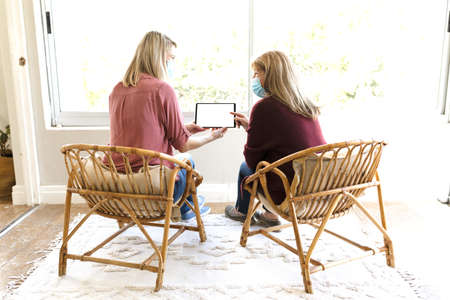 Senior Caucasian woman spending time at home with her adult daughter, sitting on couch talking and using tablet computer. Social distancing during Covid 19 Coronavirus quarantine