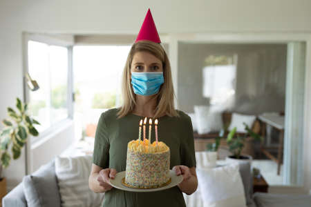 Caucasian woman spending time at home, standing in kitchen with birthday cake. Social distancing during Covid 19 Coronavirus quarantine Banco de Imagens