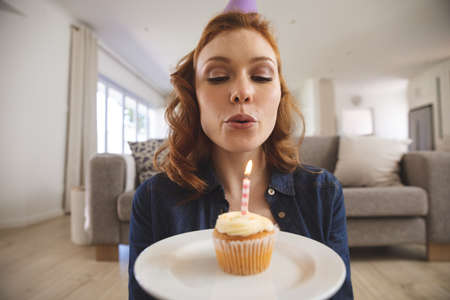 Caucasian woman spending time at home, in living room, celebrating and holding a cupcake, blowing a candle. Social distancing during Covid 19 Coronavirus quarantine lockdown.