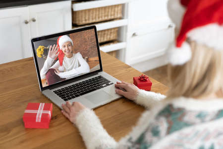 Caucasian woman spending time at home at Christmas, using laptop computer, video chatting with another woman. Social distancing during Covid 19 Coronavirus quarantine lockdown.