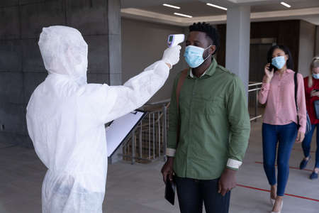 Multi ethnic group of colleagues having temperature taken by worker in protective suit before being allowed in to work. Hygiene and social distancing in workplace during Coronavirus Covid 19 pandemic.