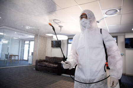 Worker wearing protective suit, face mask and gloves sanitizing office using an anti bacterial disinfectant spray. Hygiene in workplace during Coronavirus Covid 19 pandemic.