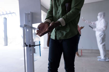 Mid sectiion of African American man sanitizing hands after health check, before entering office. Hygiene and social distancing in workplace during Coronavirus Covid 19 pandemic. Banco de Imagens