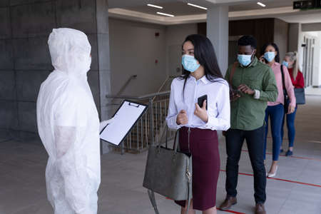 Multi ethnic group of coworkers waiting with healthcare worker in protective suit before being allowed in to work. Hygiene and social distancing in workplace during Coronavirus Covid 19 pandemic.