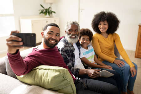 Multi generation African American family at home sitting on sofa in living room, taking selfies with smartphone, laughing. Family spending quality time at home together in slow motion.