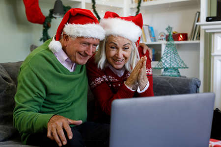 Senior couple in santa hat sitting on couch smiling while having a video call on laptop at home. social distancing during covid 19 coronavirus quarantine lockdown.