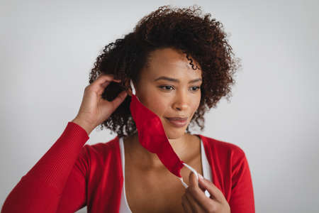Portrait of african american woman removing face mask against grey background. hygiene and precautions for infection prevention during coronavirus covid 19 pandemic. Imagens