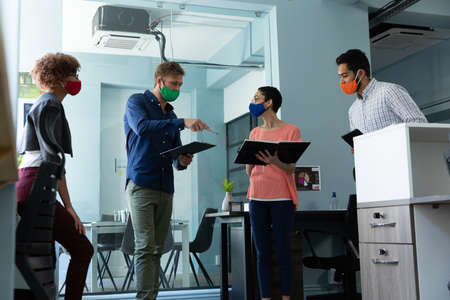 Diverse group of work colleagues wearing masks in discussion office. hygiene in workplace during coronavirus covid 19 pandemic.