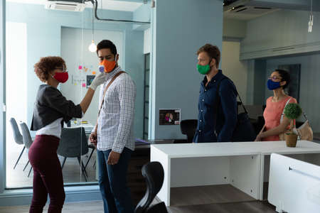 Mixed race woman wearing face mask checking temperature of colleagues. workers waiting in line to be checked. hygiene in workplace during coronavirus covid 19 pandemic Reklamní fotografie