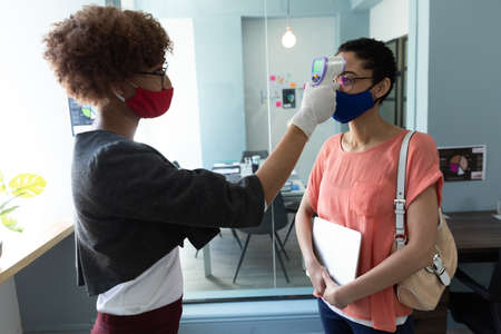 Mixed race woman wearing face mask checking temperature of female colleague. hygiene in workplace during coronavirus covid 19 pandemic