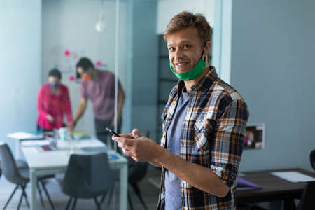 Caucasian man wearing face mask using smartphone in office. smiling to camera. hygiene in workplace during coronavirus covid 19 pandemic.