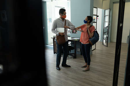 Mixed race man and woman wearing masks bumping elbows in greeting. hygiene in workplace during coronavirus covid 19 pandemic.