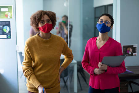 Portrait of two mixed race female colleagues wearing masks in office. hygiene in workplace during coronavirus covid 19 pandemic.