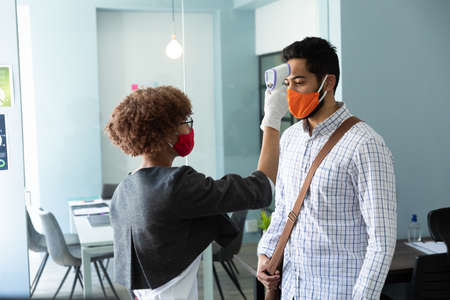 Mixed race woman wearing face mask checking temperature of male colleague. hygiene in workplace during coronavirus covid 19 pandemic Reklamní fotografie