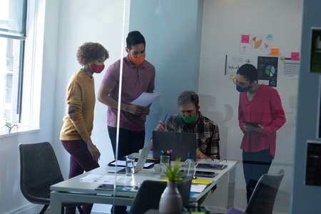Diverse group of colleagues wearing face masks discussing in office. standing and talking around one man using a laptop. hygiene in workplace during coronavirus covid 19 pandemic.
