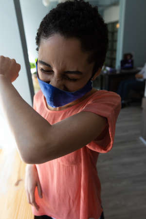 Mixed race woman wearing face mask sneezing into her elbow. hygiene in workplace during coronavirus covid 19 pandemic Reklamní fotografie
