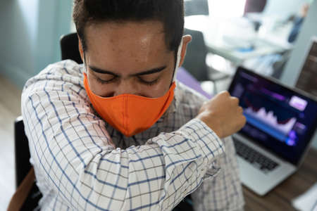 Mixed race man wearing face mask sneezing into his elbow. hygiene in workplace during coronavirus covid 19 pandemic