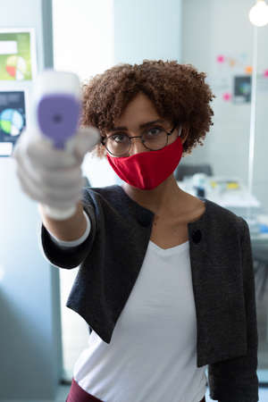 Mixed race woman wearing face mask using thermometer in office. health and hygiene in workplace during coronavirus covid 19 pandemic.