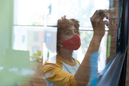 Mixed race woman wearing face mask drawing chart on glass wall in office. hygiene in workplace during coronavirus covid 19 pandemic. Reklamní fotografie