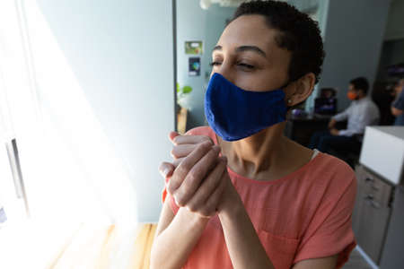 Mixed race woman wearing face mask sanitizing her hands. hygiene in workplace during coronavirus covid 19 pandemic