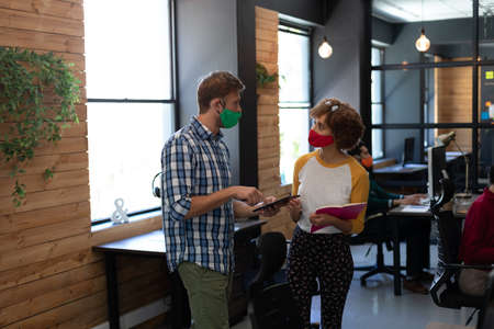 Two diverse creative colleagues wearing face masks talking in office. holding digital tablet and notebook. hygiene in workplace during coronavirus covid 19 pandemic.
