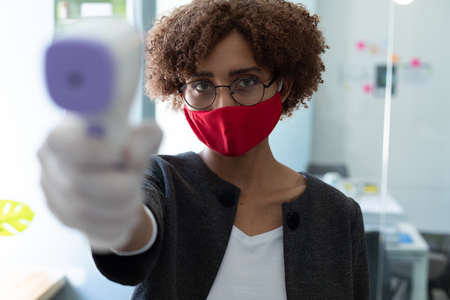 Mixed race woman wearing face mask using thermometer to check health of colleagues. hygiene in workplace during coronavirus covid 19 pandemic Reklamní fotografie