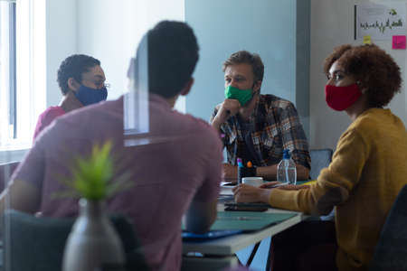 Diverse group of colleagues wearing face masks in office meeting. hygiene in workplace during coronavirus covid 19 pandemic.