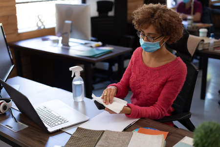 Mixed race woman wearing face mask disinfecting smartphone at her office desk. hygiene in workplace during coronavirus covid 19 pandemic. Reklamní fotografie