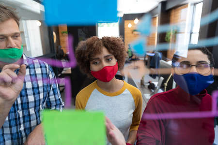 Diverse group of colleagues wearing face masks brainstorming at glass wall in office. hygiene in workplace during coronavirus covid 19 pandemic.