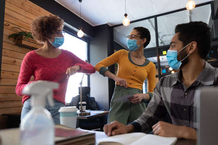 Mixed race female colleagues wearing face masks elbow bumping in office. hygiene in workplace during coronavirus covid 19 pandemic Reklamní fotografie