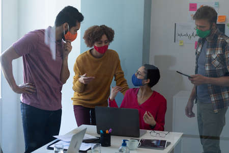 Diverse group of colleagues wearing face masks discussing in office. standing and talking around one woman sitting using laptop. hygiene in workplace during coronavirus covid 19 pandemic.