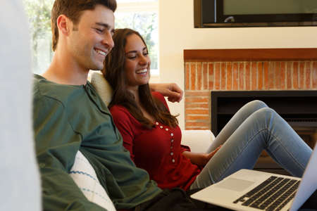 Caucasian couple having video call smiling to laptop sitting in living room. self isolation at home during covid 19 coronavirus pandemic.
